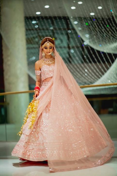 Glowing Indian Bride Kanika in a lovely blush pink lehenga for her luxury wedding in Dubai at Fairmont Ajman Hotel