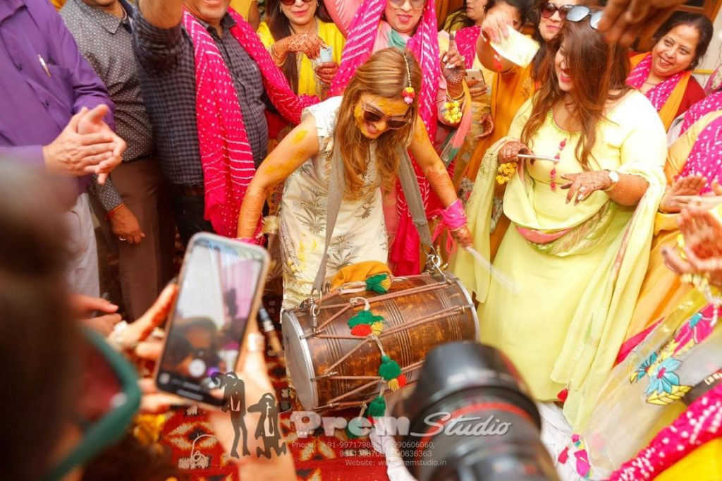 Energetic Bride playing Dhol to liven  up her Haldi Function