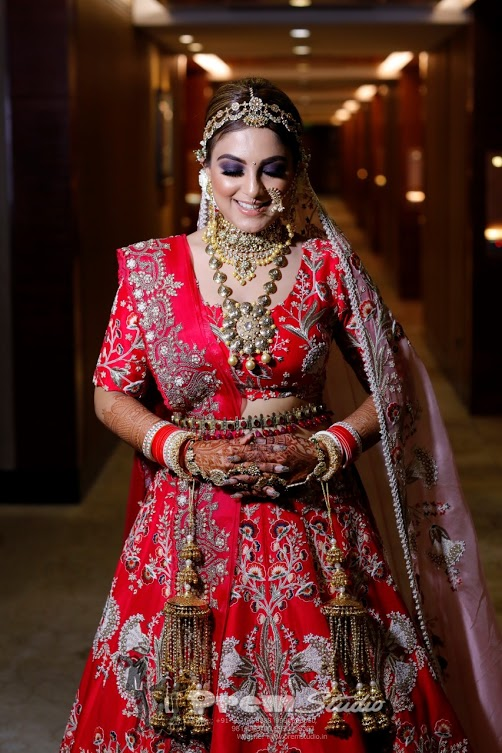 Stunning portrait of Gargi in a beautiful red bridal lehenga from Ankarkali for her Ritz Gurgaon Wedding