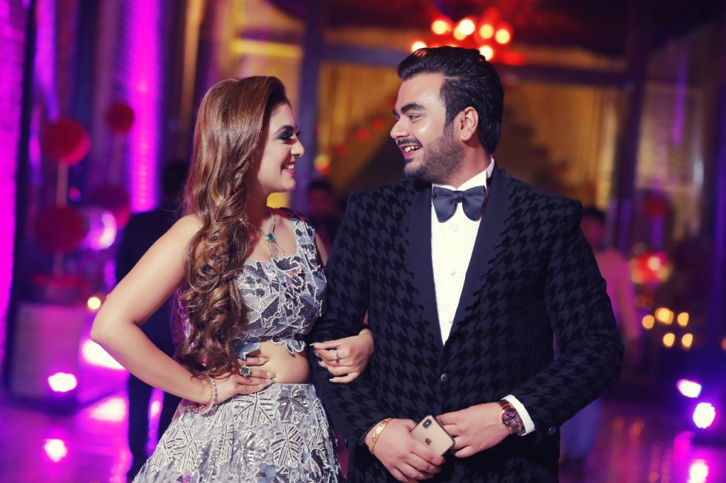 Gargi & Saurabh cute candid couple portrait at their cocktail ceremony with Gargi in a silver Indo western outfit & Saurabh in a tuxedo