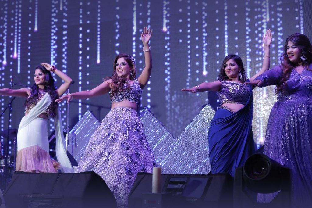 Candid shot of bride Gargi dancing with her bridesmaids at her cocktail ceremony