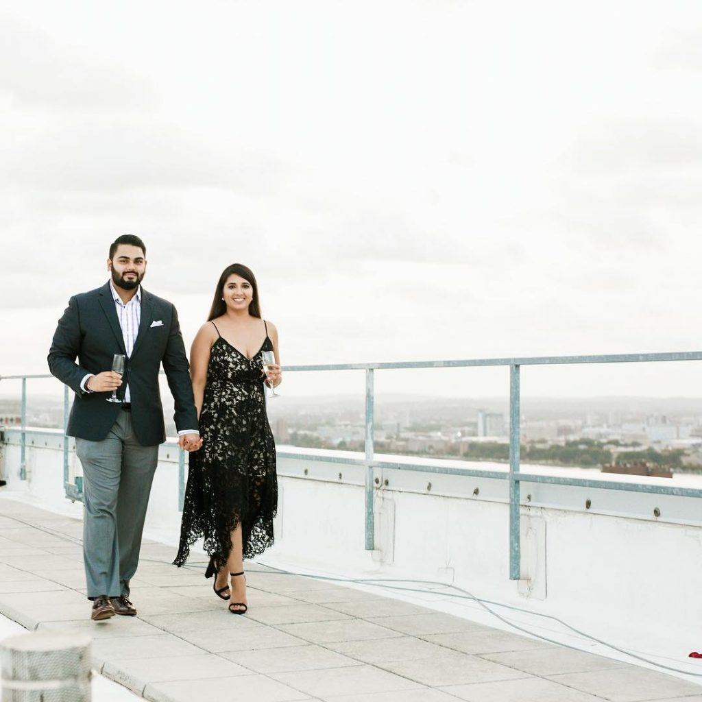 Vrunda in Black westrn outfit & Sunny in a coordinating formal suit at W Boston for a Rooftop Proposal