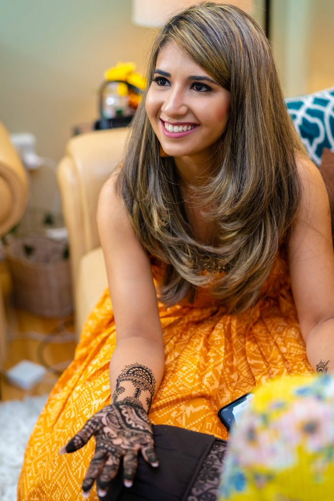 Vrunda in a bright yellow outfit applying mehendi on her hands at her intimate mehendi ceremony in Boston