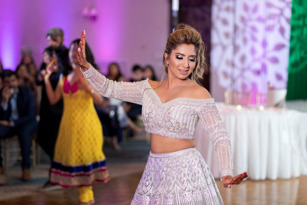 A picture of Vrunda dancing in a beautiful silver Falguni Shane peacock outfit at her forest themed wedding reception in Boston