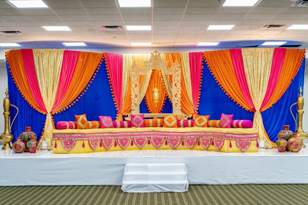 Colorful draped setup at Vrunda & sunny's indoor forest themed wedding sangeet ceremony