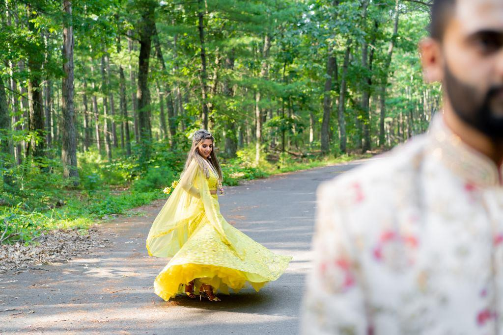 Vrunda & Sunny's phototshoot picture with Vrunda twirling in a lemon yellow outfit in forest before the sangeet ceremony