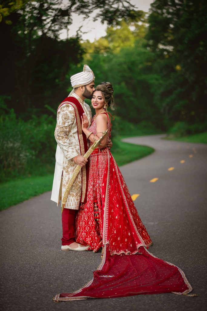 Vrunda & Sunny's cute portrait picture in coordinating wedding outfits with Vrunda in a red Anita Dongre lehengs & Sunny in a white gold sherwani with red dupatta & sword for their forest themed wedding in Boston