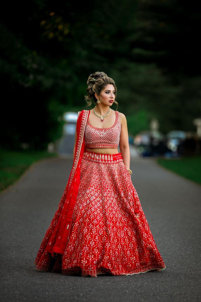 Vrunda's stylish solo picture in a red anita dongre lehenga with pockets for her forest themed wedding in Boston
