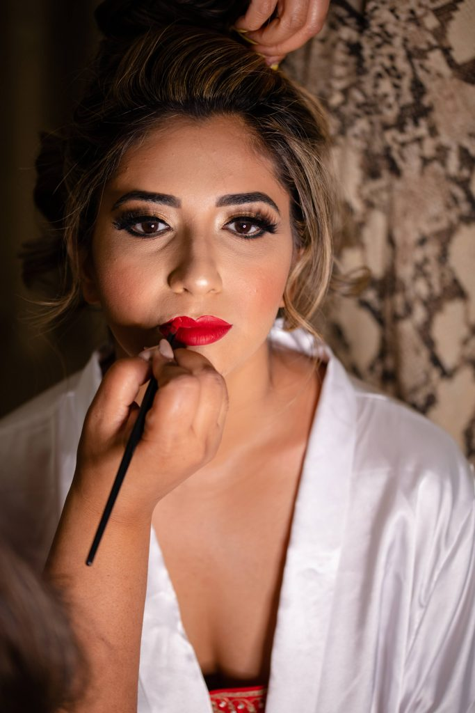 Vrunda getting ready with glam makeup look & bold red lips for her forest themed wedding