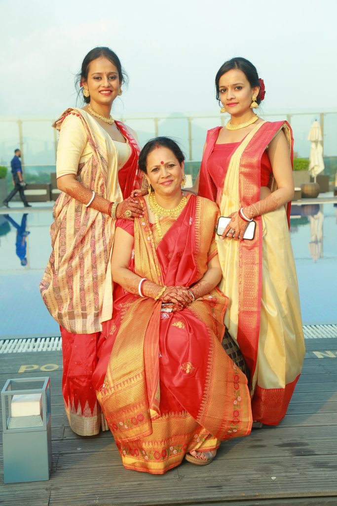 marwari bride and family in red bengali sarees and gold jewelry