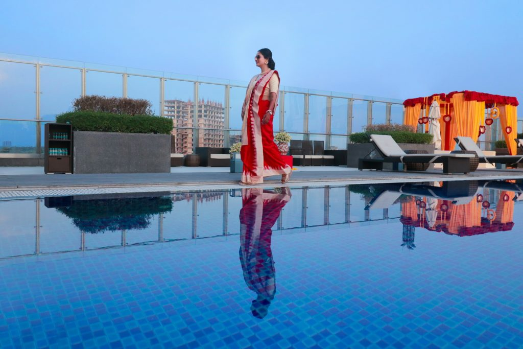 bride in a bengali saree on a poolside rooftop of westin hotel