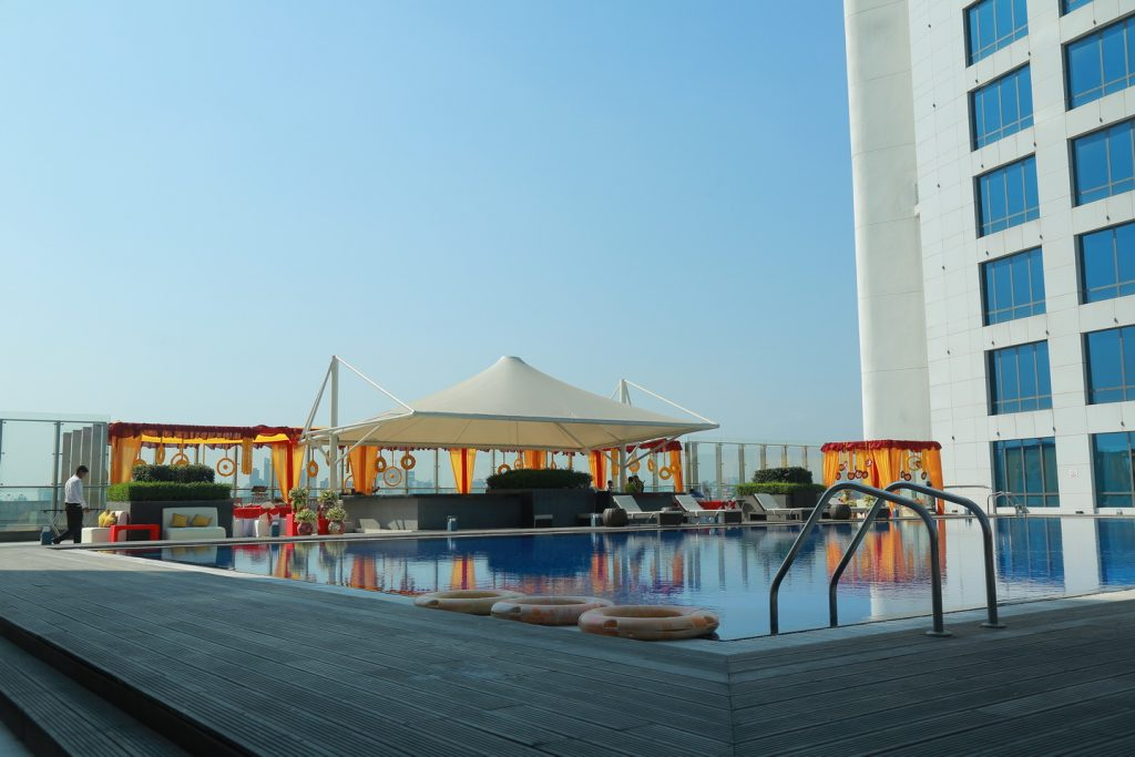mayra ceremony poolside with marigold flowers, rooftop white tents and decorations